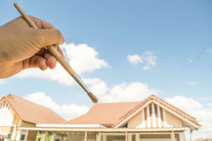 Brushing roof. An idea of roof painting with sky background stock photography