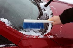 Brushing Snow off from the Windows of a Red Car. Cleaning the windows of a red car during winter. There is some snow on top of the car and a person is brushing royalty free stock photo