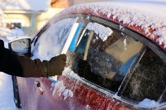 Brushing Snow off from the Windows of a Red Car. Cleaning the windows of a red car during winter. There is some snow on top of the car and a person is brushing royalty free stock image