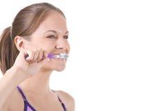 Brushing Teeth. Beautiful woman on white brushing her teeth Royalty Free Stock Photo