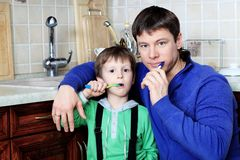 Brushing teeth. Happy father with his son brushing their teeth at home royalty free stock image
