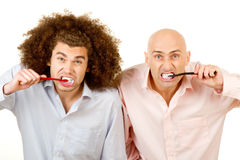 Brushing Teeth. Two men brushing their teeth. Isolated against a white background stock image