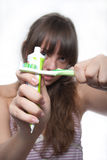 Brushing teeth. The girl with the crossed tooth-paste and a brush in hands Stock Image