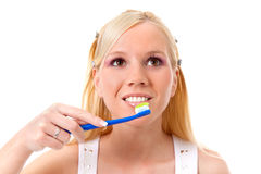 Brushing teeth. Pretty young woman is brushing her teeth, isolated on white background royalty free stock images