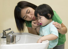 BRUSHING TEETH. Mother help child girl clean brush teeth Stock Images