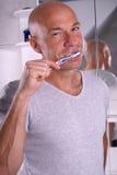 Brushing teeth. Man brushing teeth and smiles Stock Photography