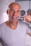 Brushing teeth. Man brushing teeth and smiles Royalty Free Stock Photo