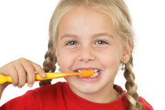 Brushing teeth. Funny girl brushing her teeth stock photo