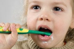 Brushing teeth. Funny girl brushing her teeth Royalty Free Stock Images