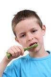 Brushing teeth. 7 years old boy brushing teeth on white royalty free stock photo