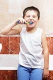 Brushing teeth in bathroom Stock Photos