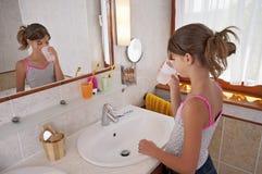 Brushing teeth in bathroom Stock Images