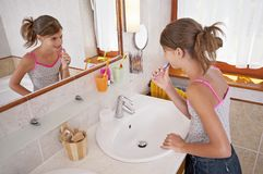 Brushing teeth in bathroom. Young woman brushing teeth in bright bathroom, collection stock photography