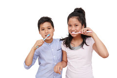 Brushing teeth. Brother and sister brushing teeth together, isolated on white royalty free stock photography
