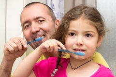 Brushing teeth. Father and daughter brushing teeth together in the bathroom Stock Photography