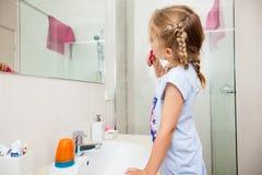 Brushing teeth. Little girl brushing her teeth in the mirror stock photo