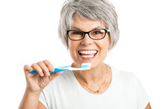 Brushing teeth. Portrait of a happy old woman brushing her teeth royalty free stock photo