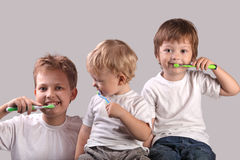 Brushing teeth. Three brothers brushing teeth together royalty free stock photography