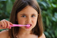 Brushing Teeth. A young toddler girl brushing her teeth with a pink toothbrush Stock Images