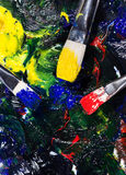Brushs avec des tubes de peinture une palette a mélangé des couleurs Photo stock