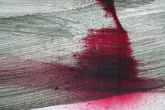 Brushstroke with black and red paint on dusty metal fence. Stroke of a brush with black and red paint on a metal fence - Abstract background-Close up royalty free stock photos