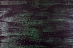 Brushstrokes with thick paint in shades of green, blue, purple on old wooden texture Royalty Free Stock Photos