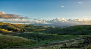 Brushy Peak Regional Reserve hills near Livermore. California. Green valley. Sunset. Blue sky with clouds in the distance. Warm light. Some stars visible Stock Photography