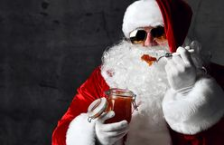 Brusque Santa Claus in aviator sunglasses is eating red caviar fish salmon. New year and Merry Christmas  concept