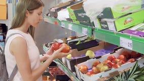 BRUSSEL, BELGIË CIRCA Augustus 2017: Jonge vrouw die appelenvruchten in supermarkt uitkiezen stock videobeelden