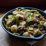 Brussel Sprouts. Bacon, brussel sprouts and cranberries in a cast iron pan Stock Image