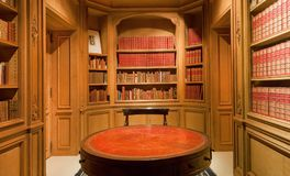 Bookshelves with old volumes of books and antique round table inside the Library stock photography