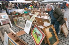 Buyer of paintings on flea market with old bargains, antique stuff, vintage decor and retro furniture. BRUSSELS, BELGIUM - APR 3: Buyer of paintings on flea Royalty Free Stock Photos