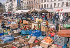Buyers of flea market looking for bargains and antique stuff in mess of vintage decor and retro details. BRUSSELS, BELGIUM - APR 3: Buyers of flea market looking Stock Image