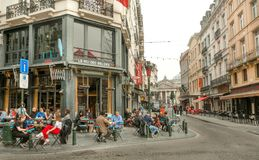 Corner street with crown of people in outdoor bar and old buildings with restaurants Royalty Free Stock Image