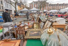 Customer of flea market and many old art, bargains and antique stuff in mess of vintage decor and retro details. BRUSSELS, BELGIUM - APR 3: Customer of flea Stock Photography