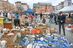 Customers of flea market and many old art, bargains and antique stuff in mess of vintage decor and retro details. BRUSSELS, BELGIUM - APR 3: Customers of flea Royalty Free Stock Images