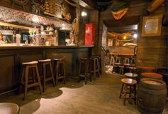 Empty bar with old wooden furniture, pirate themes decor, pub counter and barrels with wine. BRUSSELS, BELGIUM - APR 2: Empty bar with old wooden furniture Royalty Free Stock Image