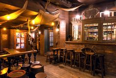Interior of old schooner style bar with old wooden furniture, pirate themes decor, pub counter and barrels. BRUSSELS, BELGIUM - APR 2: Interior of old schooner Royalty Free Stock Image