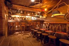 Interior of retro style bar with old wooden furniture, pirate themes decor, pub counter and barrels. BRUSSELS, BELGIUM - APR 2: Interior of retro style bar with Stock Image