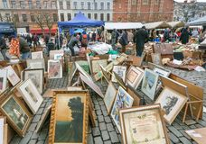 Many paintings for sale on outdoor flea market with old bargains, antique stuff, vintage decor, retro furniture. BRUSSELS, BELGIUM - APR 3: Many paintings for Stock Photography