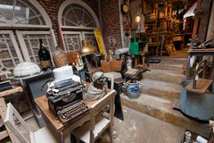 Old antique store with many vintage utensil, decor, wooden furniture, retro typewriter and many details stock photography
