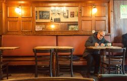 Older man alone writing letter inside old bar of cafe with historical interior and evening light. BRUSSELS, BELGIUM - APR 2: Older man alone writing letter stock images