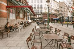 Street cafe with steel furniture, drinking people and old buildings with restaurants Stock Photo