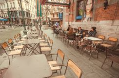 Street tables of outddor cafe with furniture, drinking people and old buildings with restaurants Stock Photography