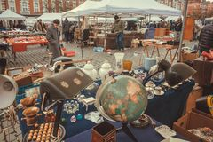 Street traders on flea market with old art, bargains and antique stuff, vintage decor and retro details. BRUSSELS, BELGIUM - APR 3: Street traders on flea market Stock Image