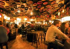 Visitors of huge bar drinking and talking in lights of vintage beer restaurant royalty free stock photography