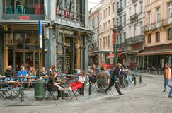 Walking people at corner street with drinkers of outdoor bar and old buildings with restaurants Royalty Free Stock Images