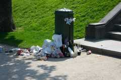 Brussels, Belgium - April 21 2018: Overflowing public trashcan on sunny day at la Cambre park royalty free stock photography