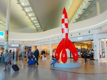 People in the duty-free shopping area with the large Tin Tin rocket at Brussels Airport stock photography