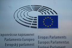 Multilingual sign and EU flag on European Parliament building in Brussels royalty free stock photos